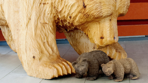 A large wooden sculpture of a bear leaning down towards two small wooden bears standing in front of it.